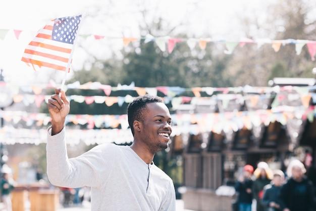 Glücklicher schwarzer mann, der amerikanische flagge wellenartig bewegt