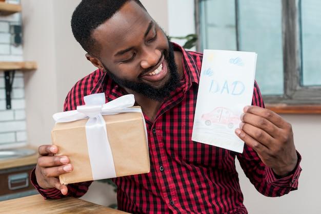 Glücklicher schwarzer mann, der grußkarte und geschenk hält