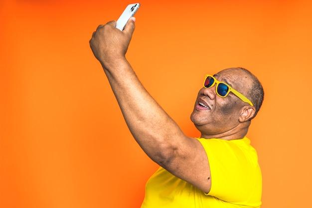Glücklicher schwarzer mann, der handy auf lokalisiertem hintergrund verwendet konzept der technologie und der kommunikationen in den alten leuten