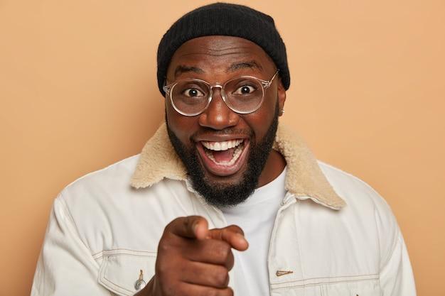 Glücklicher schwarzer mann mit zahnigem lächeln, ohrring, dickem bart, der zeigt