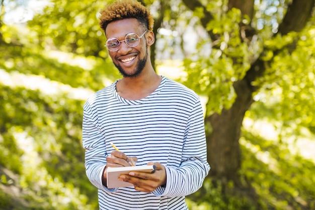Glücklicher schwarzer mann posiert mit notizblock