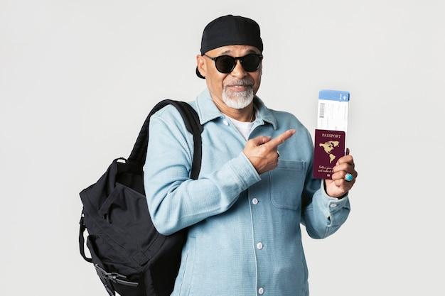 Glücklicher schwarzer seniorenreisender mit flugticket und reisepass