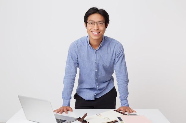 Glücklicher selbstbewusster asiatischer junger geschäftsmann in gläsern mit kopfhörern, die nahe dem tisch mit laptop lokalisiert über weißer wand stehen
