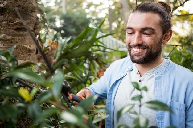 Glücklicher selbstbewusster gärtner, der heckenscheren im garten verwendet