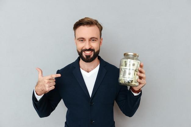 Glücklicher selbstbewusster mann, der auf box mit geld zeigt, isoliert
