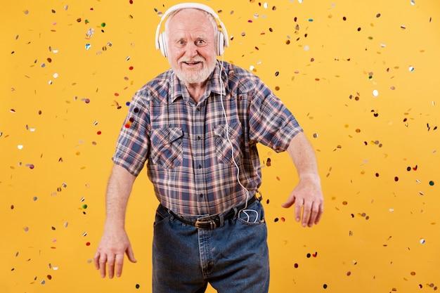 Glücklicher senior, der musikparty zu hause hat
