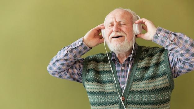 Glücklicher senior des niedrigen winkels, der musik genießt