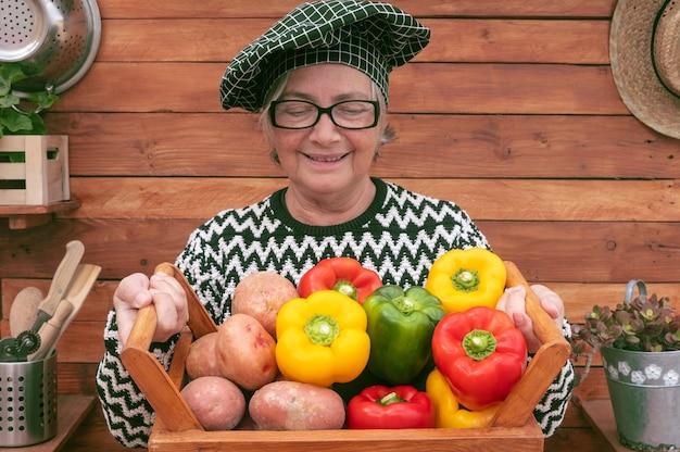 Glücklicher senior farmer hält einen holzkorb voller frisch gepflückter paprika und kartoffeln aus dem garten.