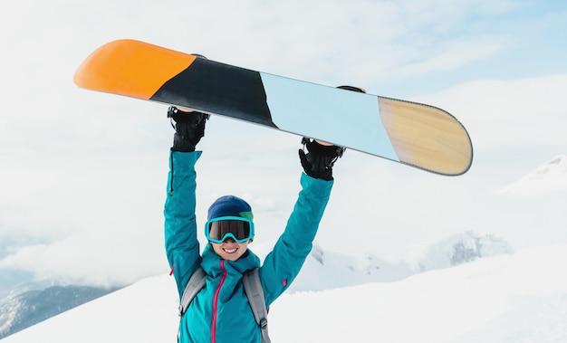 Glücklicher snowboarder der jungen frau