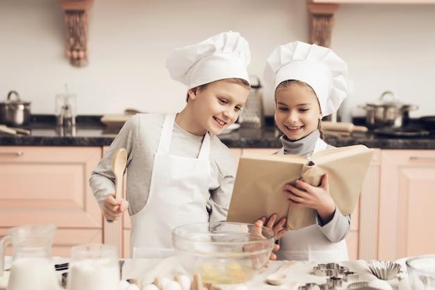 Glücklicher sohn und tochter kochen mit rezeptbuch.