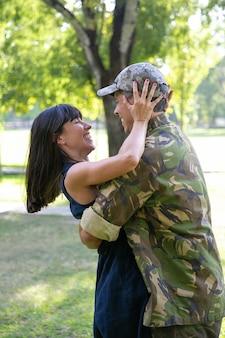 Glücklicher soldat, der seine frau im stadtpark umarmt. hübsche kaukasische frau, die freund von der armee trifft, ihn umarmt und glücklich lächelt. fröhliches paar, das sich ansieht. liebe und rückkehr nach hause konzept