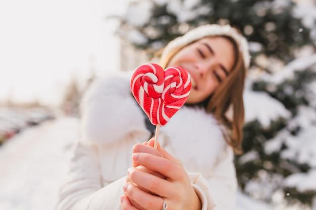 Glücklicher sonniger wintermorgen der freudigen frau, die nahaufnahme rosa herz lollypop auf straße hält. süße zeit, leckeres, kaltes wetter, schnee, strahlende gefühle, spaß haben