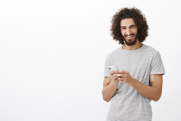 Glücklicher sorgloser gutaussehender kerl mit bart und afro-haarschnitt, smartphone haltend und lachend