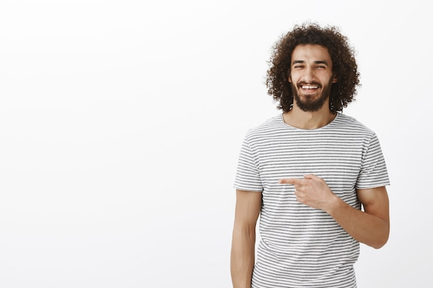 Glücklicher sorgloser gutaussehender mann mit bart im stilvollen gestreiften t-shirt, der vor freude lacht und mit dem zeigefinger nach links zeigt