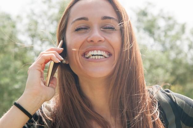 Glücklicher sorgloser kunde, der am telefon spricht