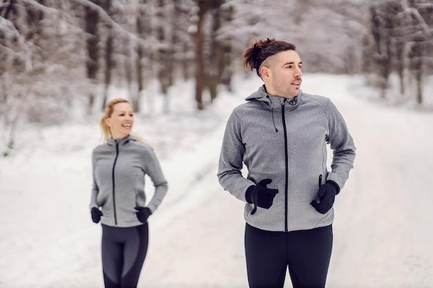 Glücklicher sportler, der am verschneiten wintertag mit seinem freund in der natur läuft. gesunder lebensstil, freundschaft, erfolg