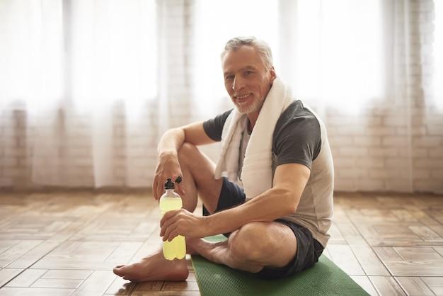 Glücklicher sportler des gesunden aktiven großvaters mit tuch.