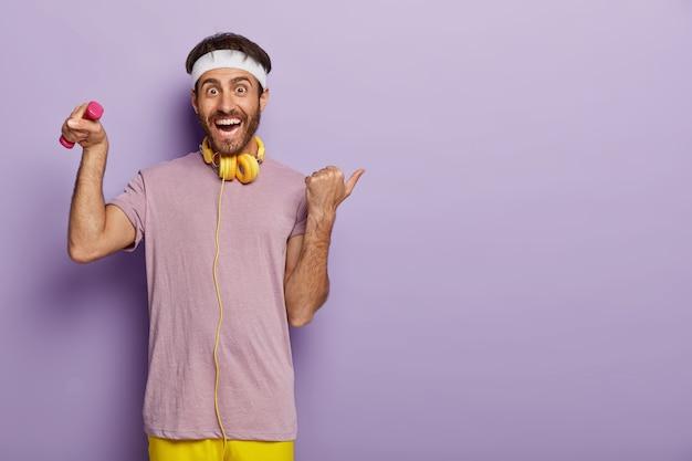 Glücklicher sportler hebt arm mit hantel, hat sporttraining drinnen, trägt stirnband und lässiges violettes t-shirt, hört musik in kopfhörern während des trainings, zeigt mit dem daumen weg auf den kopierplatz rechts