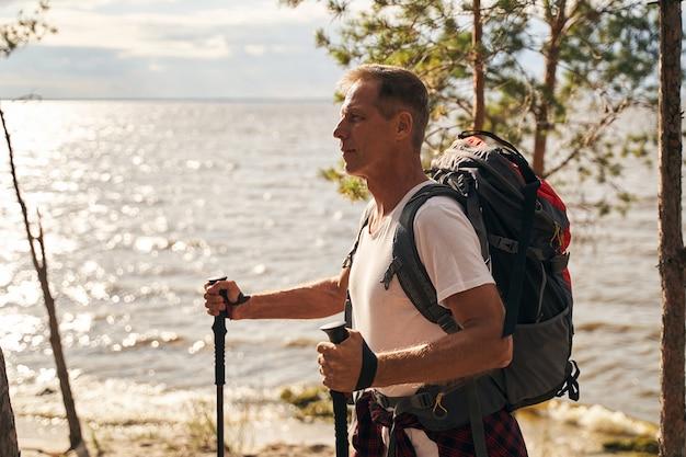 Glücklicher sportlicher mann genießt die natur beim nordic walking im wald am meer mit touristischem rucksack