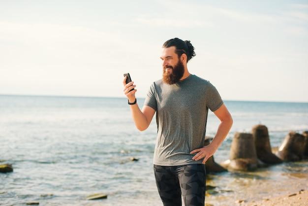 Glücklicher sportlicher mann liest eine nachricht am telefon, während er eine pause vom laufen macht.