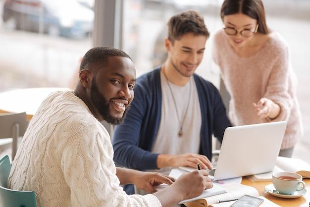 Glücklicher startupper. jugendlicher bärtiger mann macht sich notizen über den hintergrund seiner kollegen, die mit laptop diskutieren.