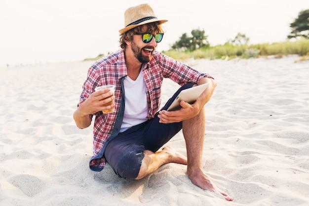 Glücklicher stilvoller mann, der tablette verwendet und bier am strand trinkt