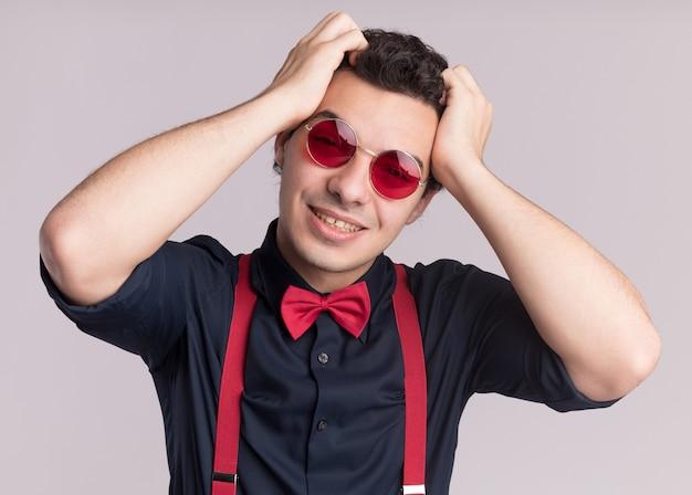 Glücklicher stilvoller mann mit fliege, die brille und hosenträger trägt, schaut nach vorne lächelnd mit händen auf seinem kopf, der über weißer wand steht