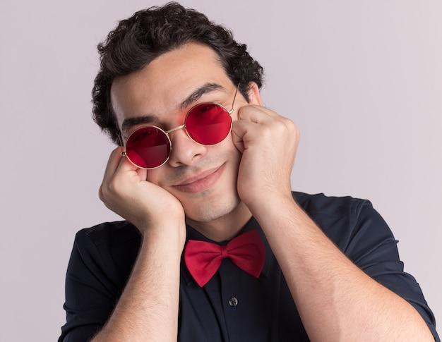 Glücklicher stilvoller mann mit fliege, die brille und hosenträger trägt, schaut vorne mit lächeln auf gesicht, das über weißer wand steht