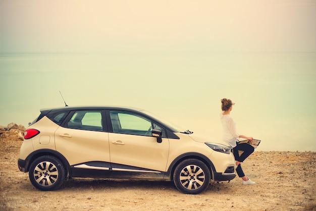 Glücklicher stilvoller reisender der jungen frau auf der strandstraße, die auf weißem kreuzauto sitzt
