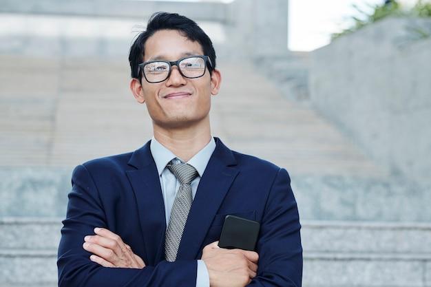 Glücklicher stolzer junger asiatischer geschäftsleiter in glases, die smartphone halten und in die kamera lächeln