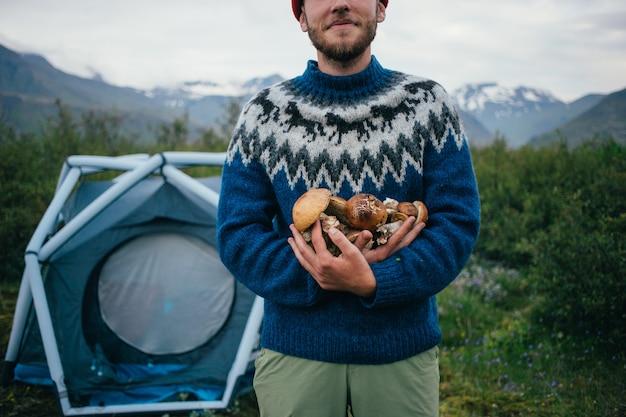 Glücklicher, stolzer pflückermann im traditionellen blauen wollpullover mit verzierungen steht auf campingplatz in den bergen, hält in den armenhaufen köstliche und organische pilze