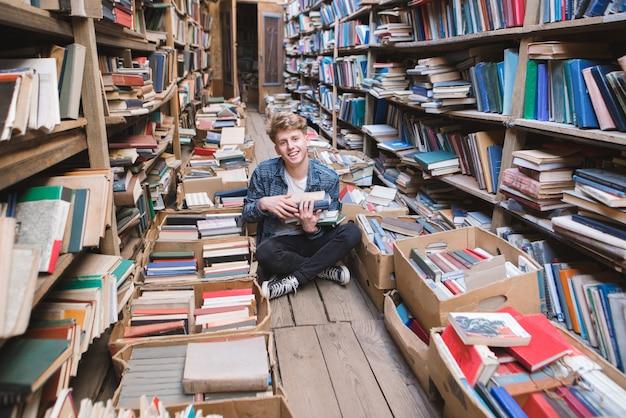 Glücklicher student, der auf dem boden in einer alten öffentlichen bibliothek sitzt und beschäftigte selbstbildung.
