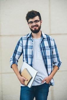 Glücklicher student, der auf der kamera draußen hält texrbooks aufwirft
