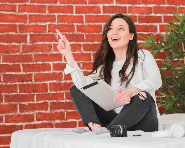 Glücklicher student, der im bett mit digitalem tablett sitzt