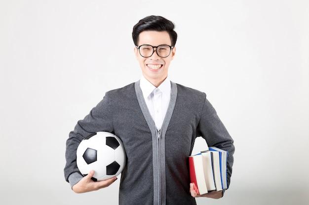 Glücklicher student im aufbaustudium, der einen stapel bücher und einen fußball hält.