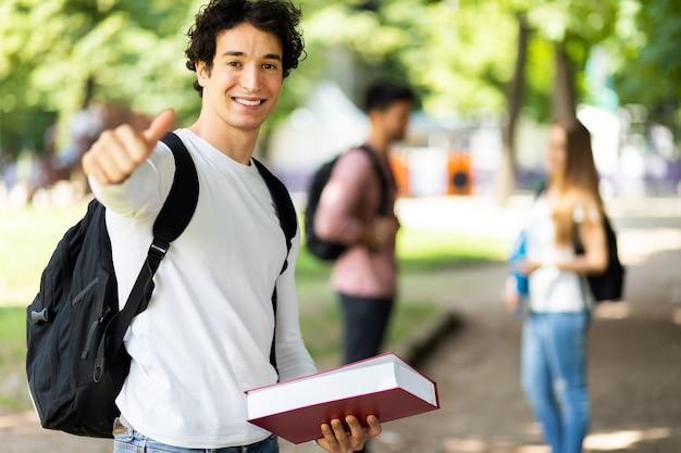 Glücklicher student im freien, der selbstbewusst lächelt und daumen aufgibt