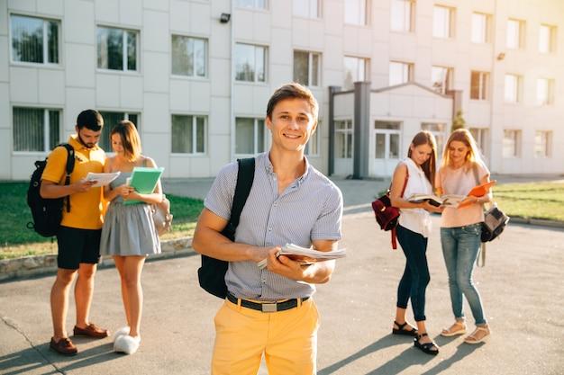 Glücklicher student mit den notizbüchern und rucksack, die bei der stellung lächeln