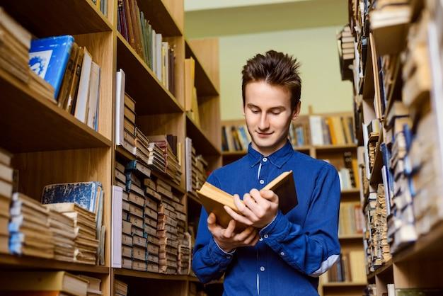 Glücklicher student mit einem buch in seinen händen in der bibliothek