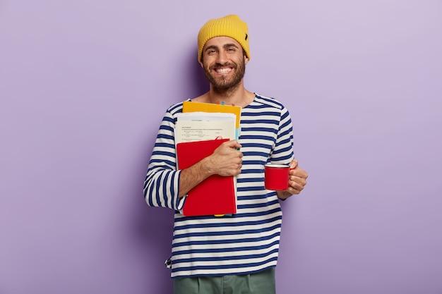 Glücklicher student trägt papiere und notizblock, bereitet sich auf prüfungen vor, trinkt heißes getränk aus der tasse