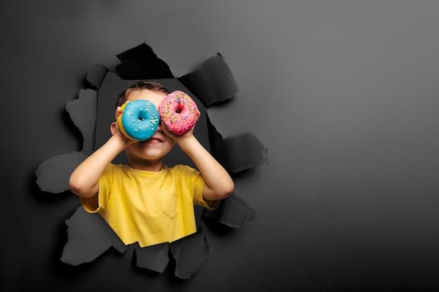 Glücklicher süßer junge hat spaß, der mit donuts an der schwarzen wand gespielt wird.