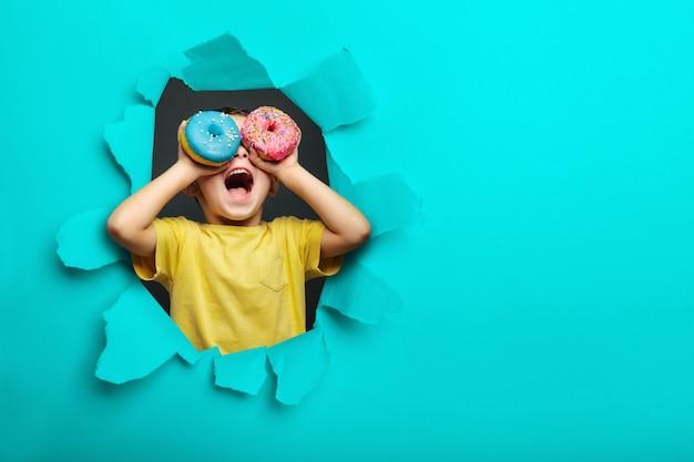 Glücklicher süßer junge hat spaß, der mit donuts auf schwarzer hintergrundwand gespielt wird. helles foto eines kindes.