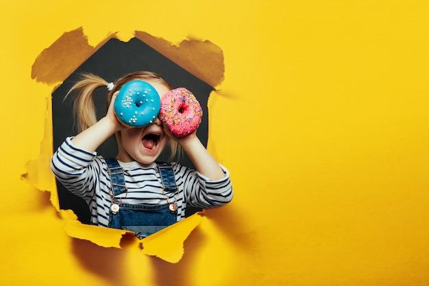 Glücklicher süßer junge hat spaß, der mit donuts auf schwarzer hintergrundwand gespielt wird.