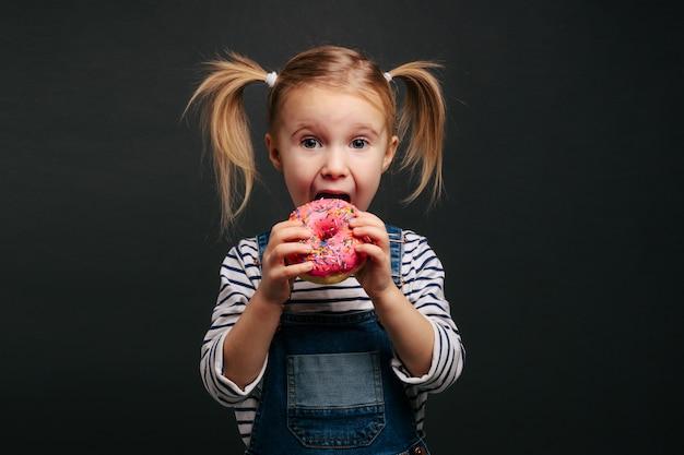 Glücklicher süßer junge hat spaß, der mit donuts gespielt wird