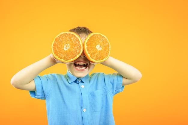Glücklicher süßer junge hat spaß, der mit fruchtorange auf gelber hintergrundwand gespielt wird.