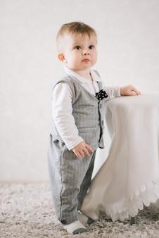 Glücklicher süßer junge im anzug eines herrn steht nahe der stütze auf einem hellen hintergrund, versucht aufzustehen und lernt laufen.
