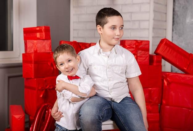 Glücklicher süßer kinderjunge geben freund zwei schönen kindern geschenk
