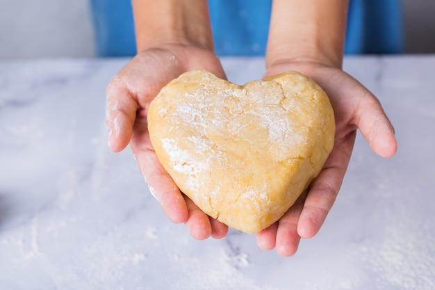 Glücklicher süßer kleiner junge, der in den händen ein herzförmiges stück hausgemachten teig hält familienzeit in der gemütlichen küche. winteraktivität zu hause. hilfe und hausaufgabentraining für kinder