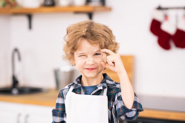 Glücklicher süßer kleiner junge in der schürze, der sternförmigen cutter durch sein auge hält, während kekse in der küche machen