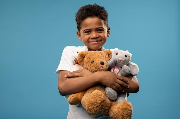Glücklicher süßer kleiner junge mit zwei stofftieren und teddybär, der sie beim spielen anlächelt