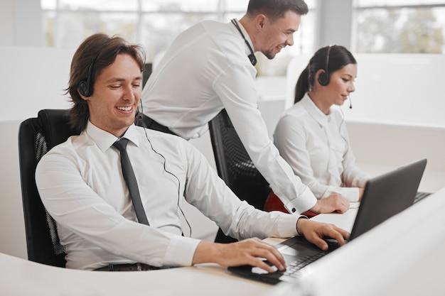 Glücklicher support-mitarbeiter, der laptop in der nähe von kollegen verwendet